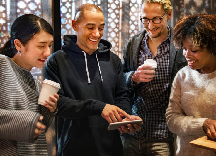 group of men and women smiling while looking at phone